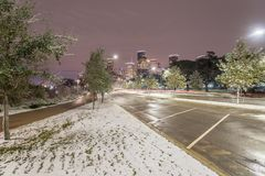Unusual snow in Downtown Houston and snowfall at Eleanor Park. Downtown Houston at  night with big and fluffy snowflakes fell on grass near parking lots at Royalty Free Stock Image