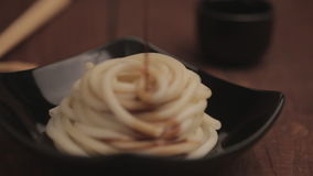 Unusual Soy Pasta. Pasta poured with soy sauce in beautiful black plate on brown wooden table with chopsticks and a cup of sake in the background. Shallow dof stock video