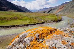 Unusual stone formations with colored patches of lichen and moss on the background of mountains and river Royalty Free Stock Images
