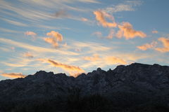Unusual sunset clouds over the  mountains in Tucson, Arizona. Desert mountain landscape with huge clouds Stock Photos
