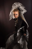 Unusual theatrical makeup. A girl with an unusual theatrical makeup in the dark tones Stock Photos