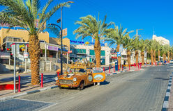 The unusual tourist car. EILAT, ISRAEL - FEBRUARY 24, 2016: The tourist car decorated with the model of the medieval town-fortress and colorful reliefs, on royalty free stock images
