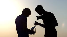 Two men look at a drone control panel in slo-mo. An unusual view of a two men looking at a modern drone control panel outdoors at a sunset in slow motion. They stock video