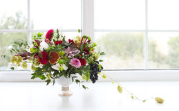 Unusual wedding composition with succulent flowers, grape, fig a. Nd hop in retro style near the window Stock Image