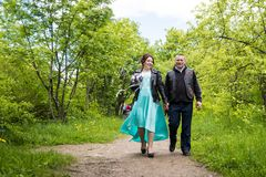 Unusual wedding couple including bride and groom in rocker leather jacket in the green park. Kirov, Russia - June 15, 2018: Unusual wedding couple including royalty free stock images