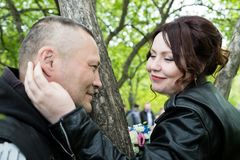 Unusual wedding couple including bride and groom in rocker leather jacket in the green park. Kirov, Russia - June 15, 2018: Unusual wedding couple including stock images