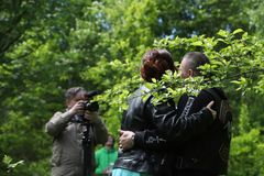 Unusual wedding couple including bride and groom in rocker leather jacket in the green park. Kirov, Russia - June 15, 2018: Unusual wedding couple including stock image