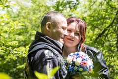 Unusual wedding couple including bride and groom in rocker leather jacket in the green park. Kirov, Russia - June 15, 2018: Unusual wedding couple including stock photo