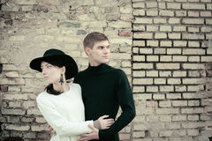 Unusual young couple love in spring with brick wall Royalty Free Stock Image