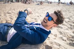 Unusual young man in elegant suit relaxes on the beach and laughs. Funny guy lies down on the sand and has time to rest royalty free stock images