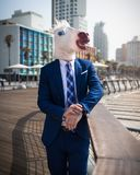 Unusual young man in elegant suit stands on the city waterfront. Strange guy in funny mask relaxes on city promenade. Cheerful unicorn is enjoying holidays on stock photos