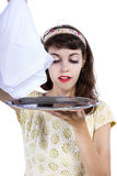 Unveiling a Surprise. Retro style female waitress unveiling a surprise hidden in a tray and napkin Royalty Free Stock Images