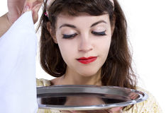 Unveiling a Surprise. Retro style female waitress unveiling a surprise hidden in a tray and napkin Stock Photos