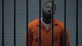 Unverschämter schwarzer Gefangener in der Zelle, die direkt zur Kamera, Schwerverbrecher schaut stock footage