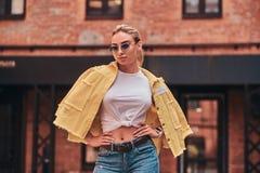 Unversch?mte modische Frau in der Sonnenbrille wirft f?r Stadtyard des Fotografen zuf?llig auf stockbild