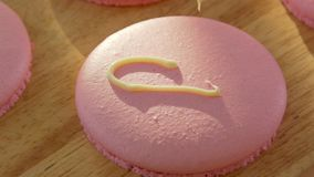 Unvisiable confest make the inscription `love`, using a pastry bag. Close-up on a pink macaroon biscuits. Unvisiable confest make the inscription love , using a stock video footage