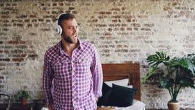 Unvorsichtiger bärtiger Mann ist tanzend und beim Hören Musik durch drahtlose Kopfhörer im Schlafzimmer gestikulierend erregt stock footage