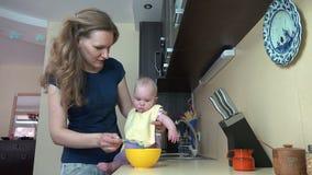 Unvorsichtiges Babysitterfrauen-Zufuhrbaby auf Tabelle in der Küche 4K stock video footage