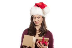 Unwanted christmas gift. Young woman is unpleasantly surprised by her christmas gift royalty free stock photos