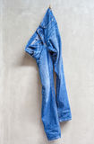 Unwashed blue jeans is hanging on the exposed concrete wall. Royalty Free Stock Images