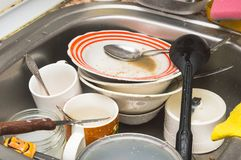 Unwashed kitchen utensils and dishes in the sink. Dirty unwashed kitchen utensils and dishes in the sink royalty free stock photography