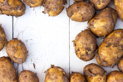 Unwashed new potatoes on white rustic wood. Space for text. Stock Image