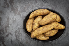 Unwashed Raw Fingerling Potatoes in Black Dish over Dark Slate O. Unwashed raw fingerling or kipfler potaotes in a black dish over dark slate background Stock Photo