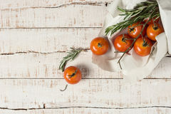 Unwashed tomatoes and sprigs of rosemary in paper. Just out of the store or market. Natural light. Healthy food background Royalty Free Stock Photos