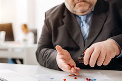 Unwell concerned man counting his pills Stock Photos