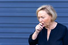 Unwell elderly lady having a coughing fit. Holding her hand to her mouth conceptual of seasonal flu, allergies or choking over blue with copy space Royalty Free Stock Image