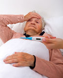 Unwell elderly woman. Lying in the bed with a thermometer Stock Photo