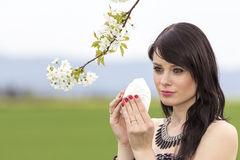 Unwell hayfever girl is pained in green spring nature. The beautiful young woman is pained by her allergy every year. She holds a tissue in her hands Stock Photo