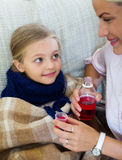Unwell little girl taking mixture from worried mother Stock Image