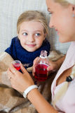 Unwell little girl taking mixture from worried mother Stock Photos