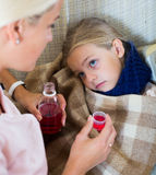 Unwell little girl taking mixture from worried mother Stock Images