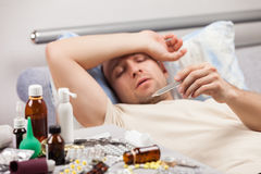 Unwell man patient lying down bed Royalty Free Stock Images