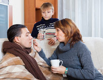 Unwell man surrounded by caring wife and  son. Unwell men surrounded by caring wife and  son in living room Stock Images
