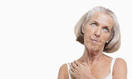 Unwell senior woman with thermometer in mouth against white background royalty free stock image