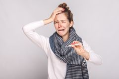 Unwell sick woman have temperature, holding head and cry. Studio shot, isolated on gray background Royalty Free Stock Images