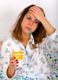 Unwell woman. Unwell beautiful woman laying in the bed and drinking hot tea Royalty Free Stock Images