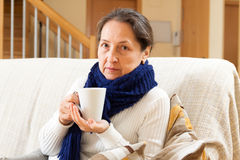 Unwell woman in blue scarf Stock Images