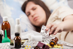 Unwell woman patient lying down bed Stock Image