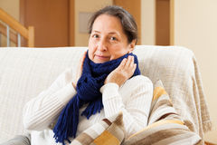 Unwell woman in scarf sitting at home Royalty Free Stock Images