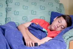 Unwell young teenage boy. Wrapped in a duvet on a sofa stock image
