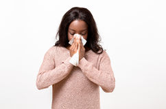 Unwell young woman blowing her nose. On a white tissue conceptual of seasonal flu and colds, allergy, rhinitis or hayfever, head and shoulders on white Royalty Free Stock Image