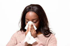 Unwell young woman blowing her nose. On a white tissue conceptual of seasonal flu and colds, allergy, rhinitis or hayfever, head and shoulders on white Royalty Free Stock Photo