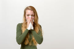 Unwell young woman blowing her nose Royalty Free Stock Image