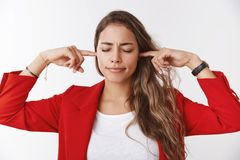 Unwilling hear. Girl shuts ears close eyes pursing lips displeased irritated cannot concentrate hearing interrupting. Bothering noise standing annoyed plugging royalty free stock photos