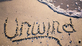 Unwind words. Words in the sand that say Unwind Royalty Free Stock Photos