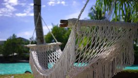 Unwinding and relaxing Holidays. A empty hammock swaying with the cool and relaxing wind on a tropical holiday resort stock footage